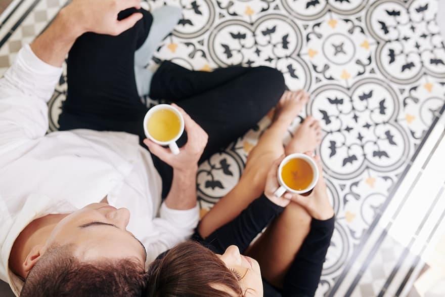 זוג צעיר יושב אחד ליד השני בדייט רומנטי ושותה מכוסות של תה