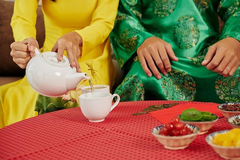 זוג של אנשים בבגדים מסורתיים מכינים תה ירוק בבית