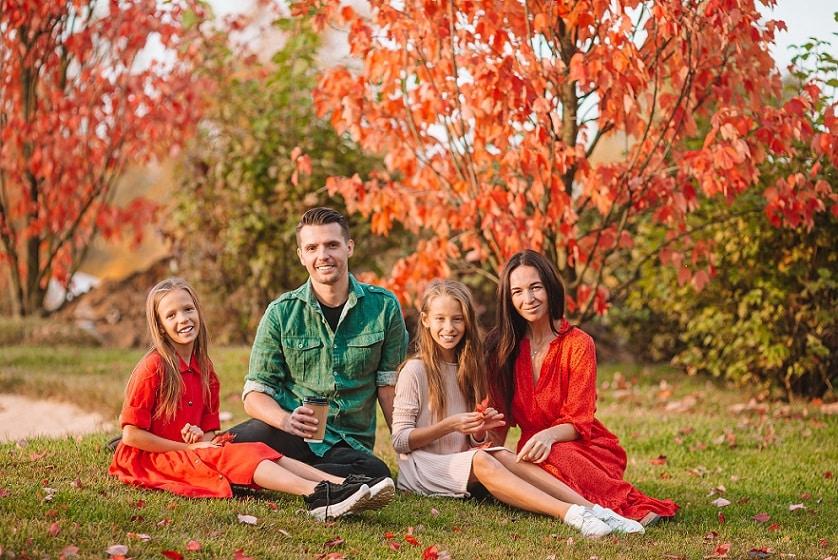 משפחה של 4 נפשות יושבת בפארק ומחייכת למצלמה על רקע של עצים פורחים בצבע אדום