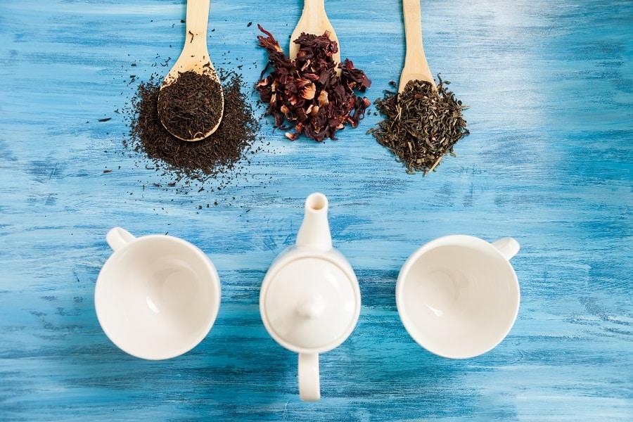 סוגים שונים של חליטות תה מונחות בתוך כפות זכוכית על השולחן