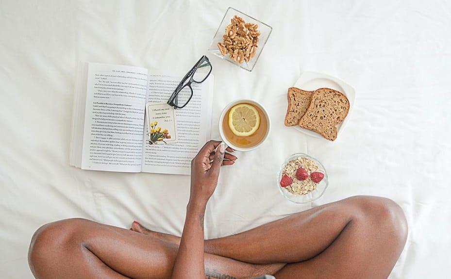 רגליים של בחורה על מיטה עם ארוחת בוקר וכוס של תה ירוק ביד