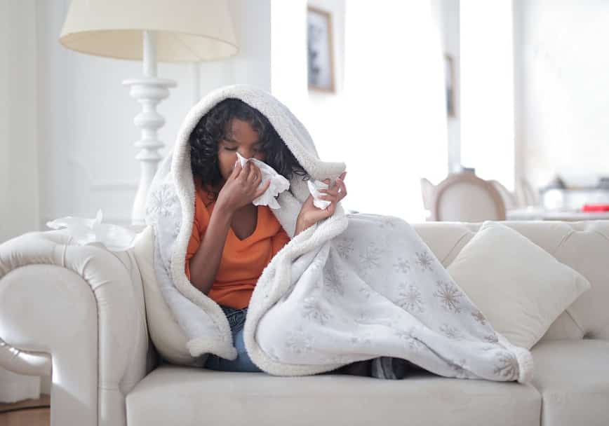 אישה שוכבת על ספה ומנגבת נזלת מהאף עם מפית