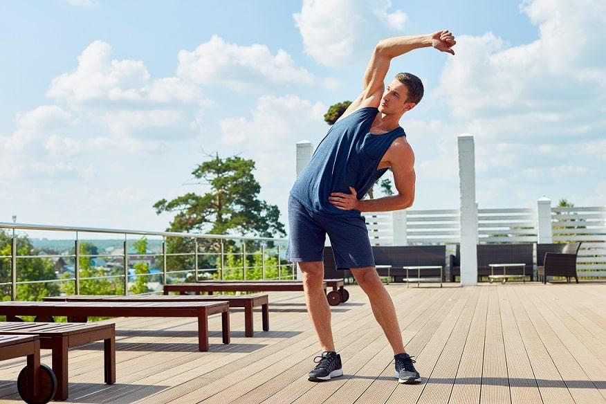 אתלט בבגדים כחולים עושה מתיחות על רצפה מעץ ורקע של שמיים