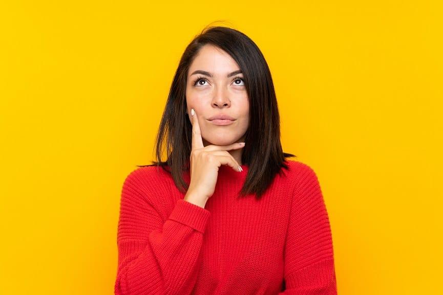 בחורה עם חולצה אדומה על רקע צהוב עושה פרצוף של שאלה