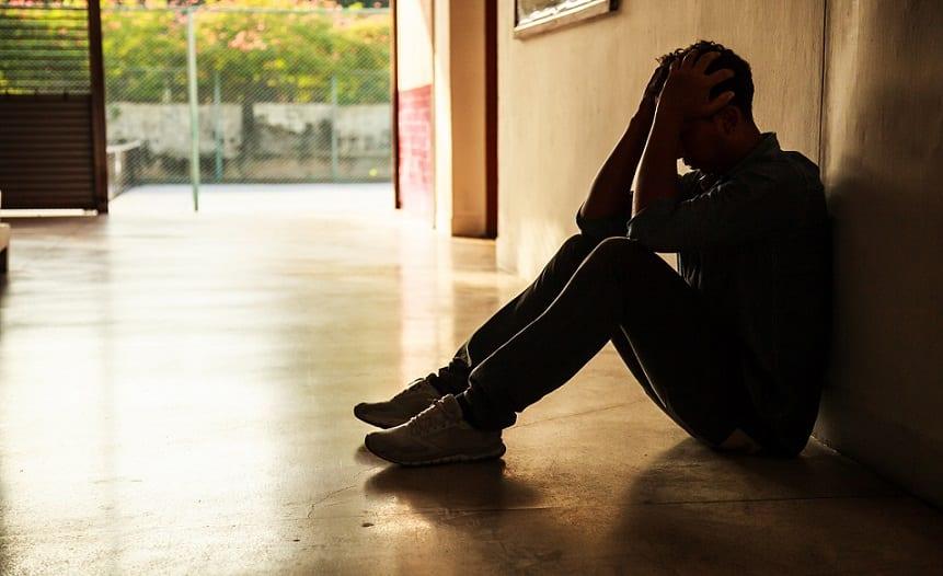 בחור יושב בכניסה לבניין עם הידיים על הראש