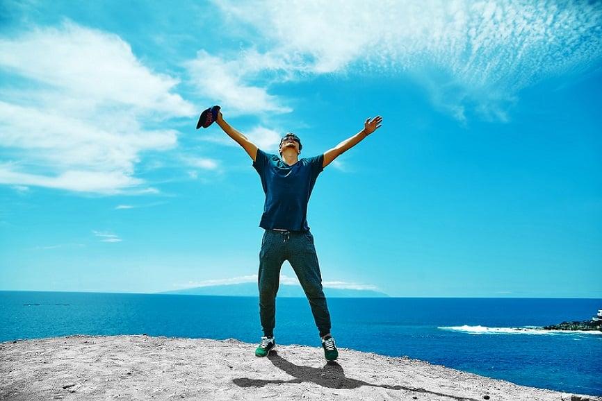 בחור עומד על הר ופורש את הידיים בתנועת ניצחון