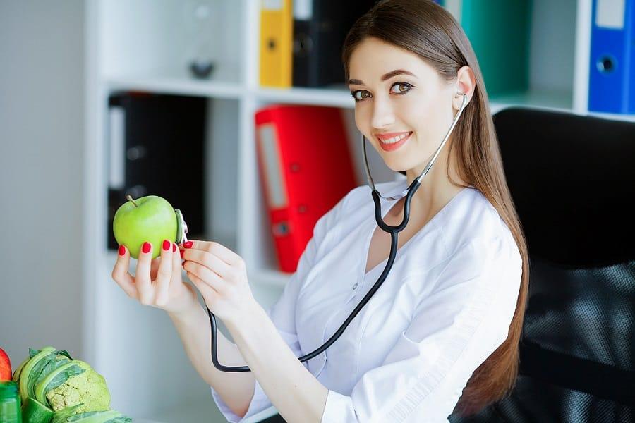 רופאה צעירה מצמידה סטטוסקופ לתפוח ירוק