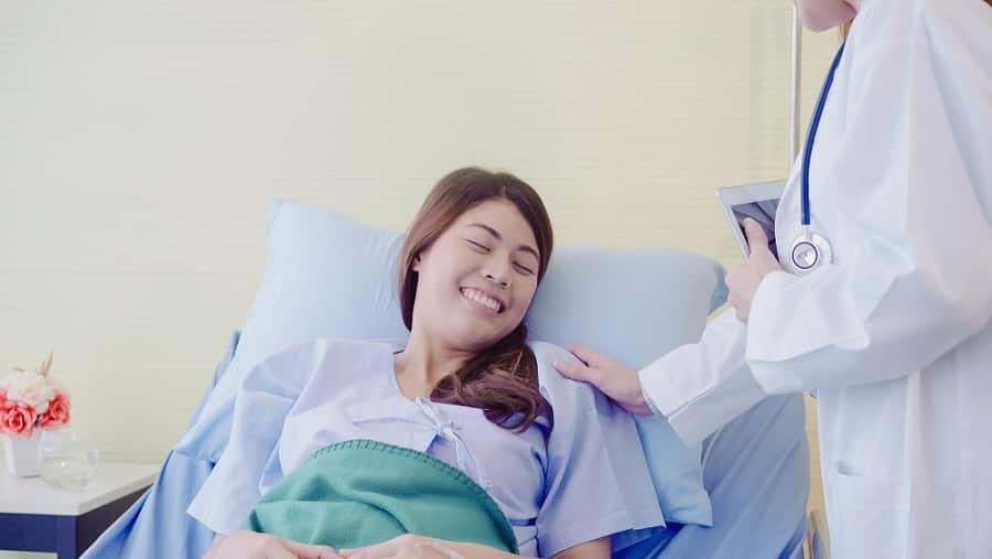 רופא מדבר עם המטופלת שלו אחרי שהיא עברה ניתוח