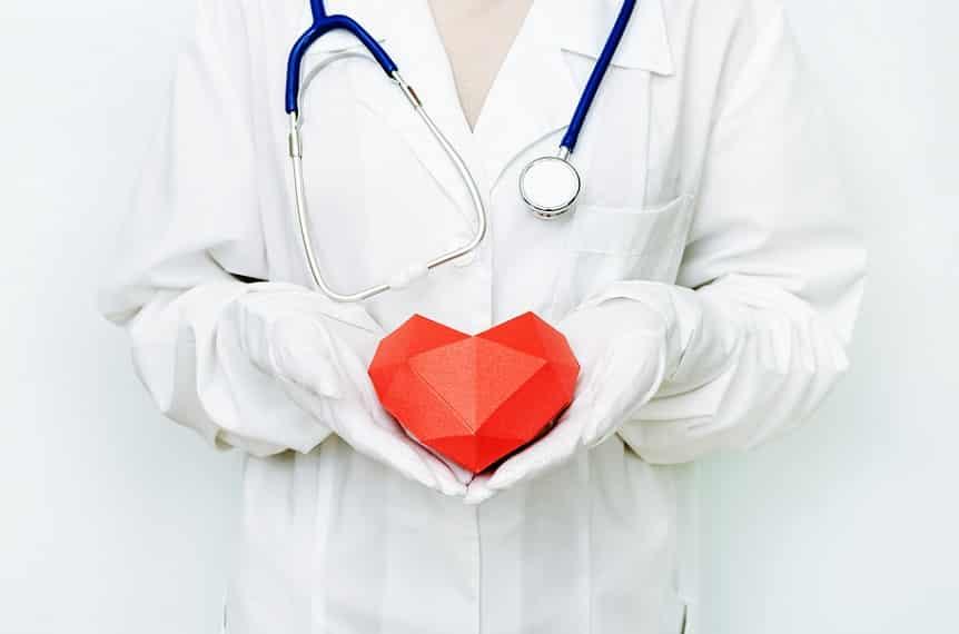 אדם בחלוק לבן מחזיק פסל קטן ואדום של לב בידיים