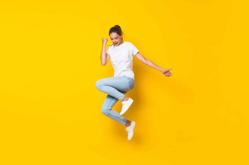 בחורה קופצת משמחה על רקע צהוב