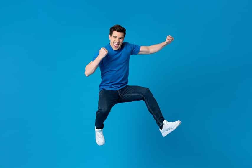 גבר קופץ משמחה על רקע כחול כהה