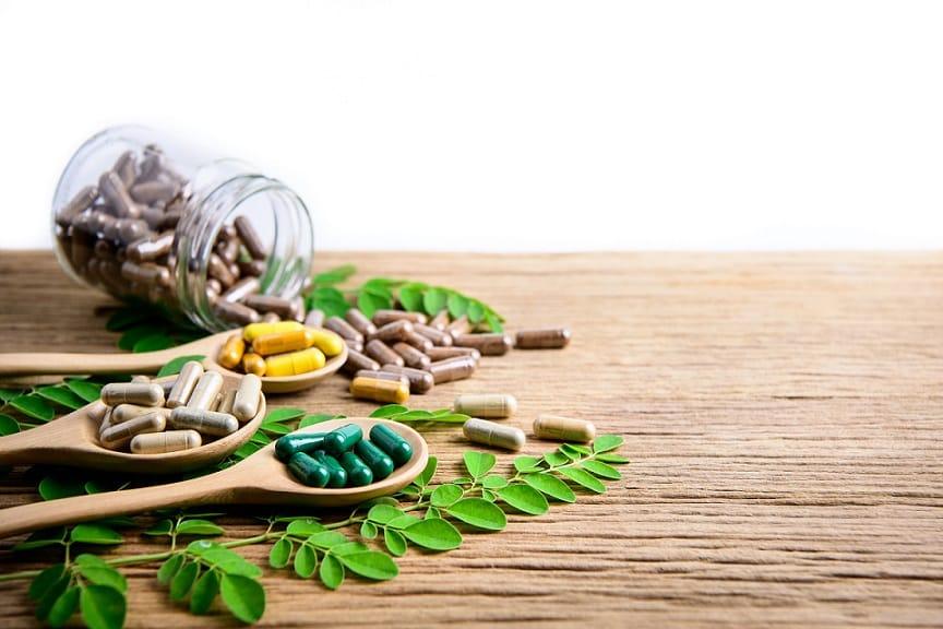 ויטמינים שונים מונחים על שולחן בכפיות ליד צמחים