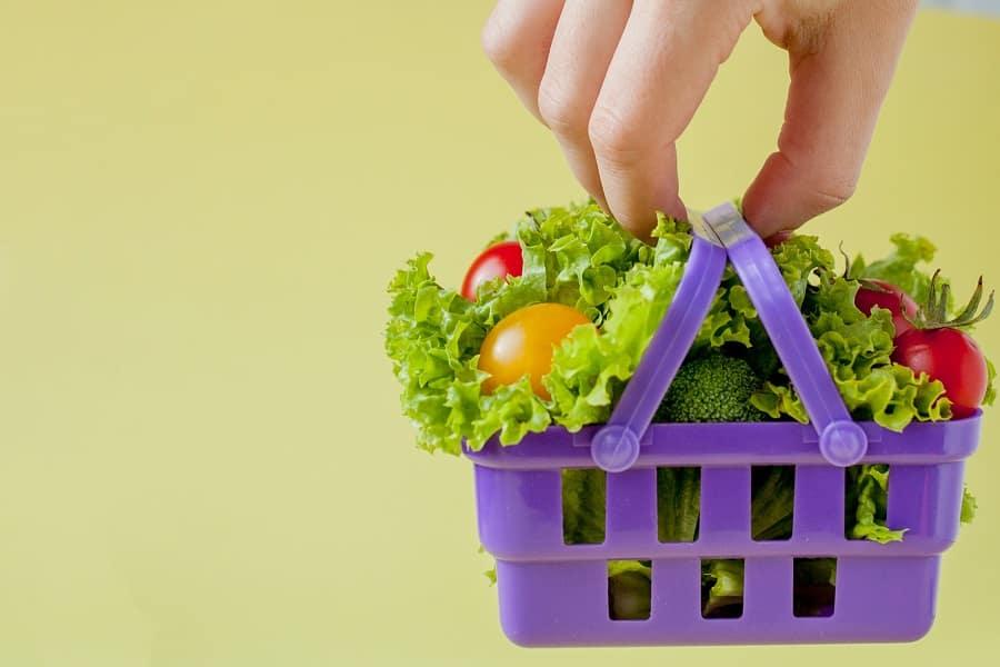 יד מחזיקה סלסלה קטנה בצבע סגול עם ירקות