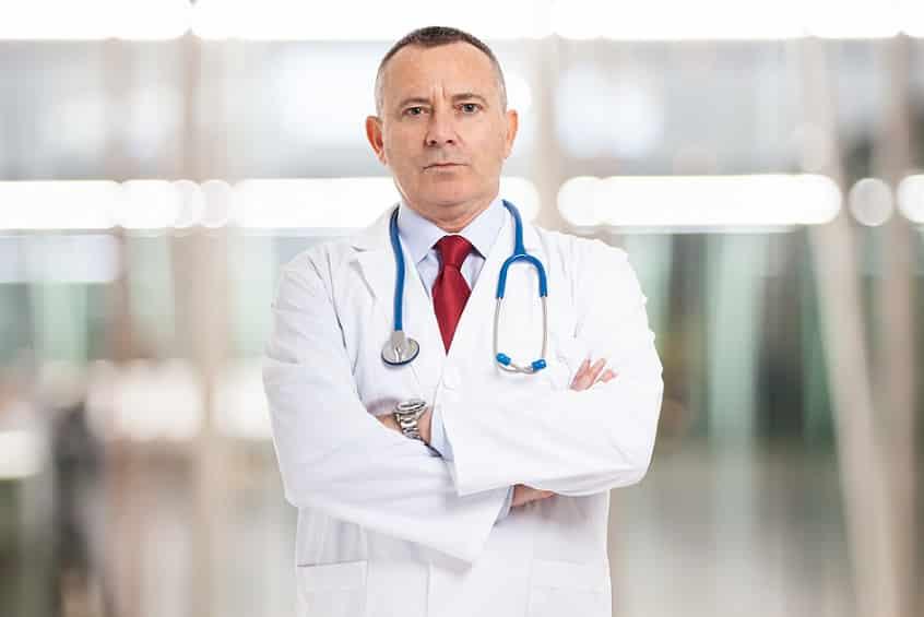 רופא עם מבט קשוח משלב ידיים ומביט למצלמה
