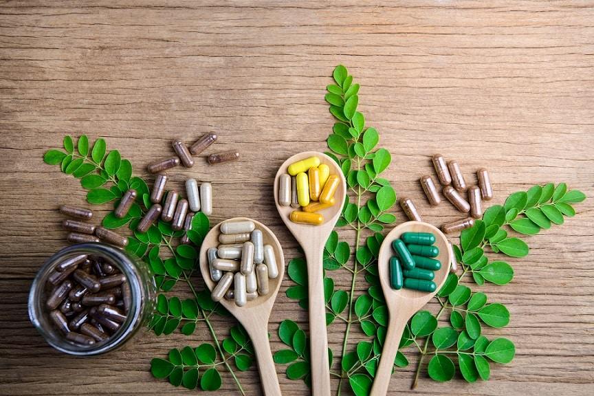 תוספי תזונה שונים מונחים בתוך כפות מעץ