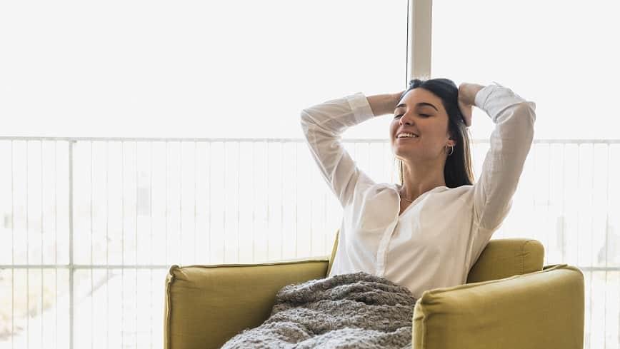 אישה יושבת על ספה ונשענת אחורה בהנאה