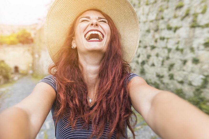 בחורה עוצמת עיניים מסתכלת למעלה ומחייכת מאושר ברחוב