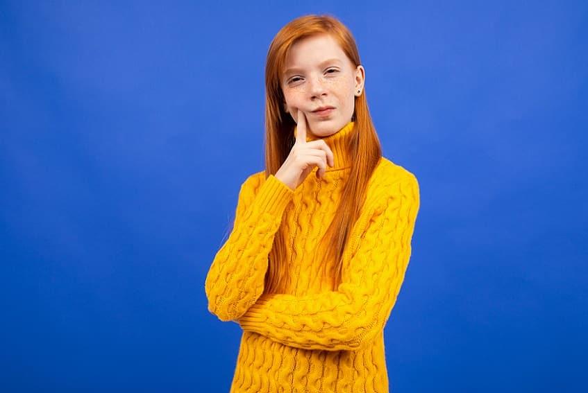 בחורה עם סוודר צהוב עושה פרצוף חושב ומסוקרן