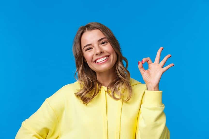 בחורה צעירה מחייכת ועושה סימן של הכל מעולה על רקע כחול