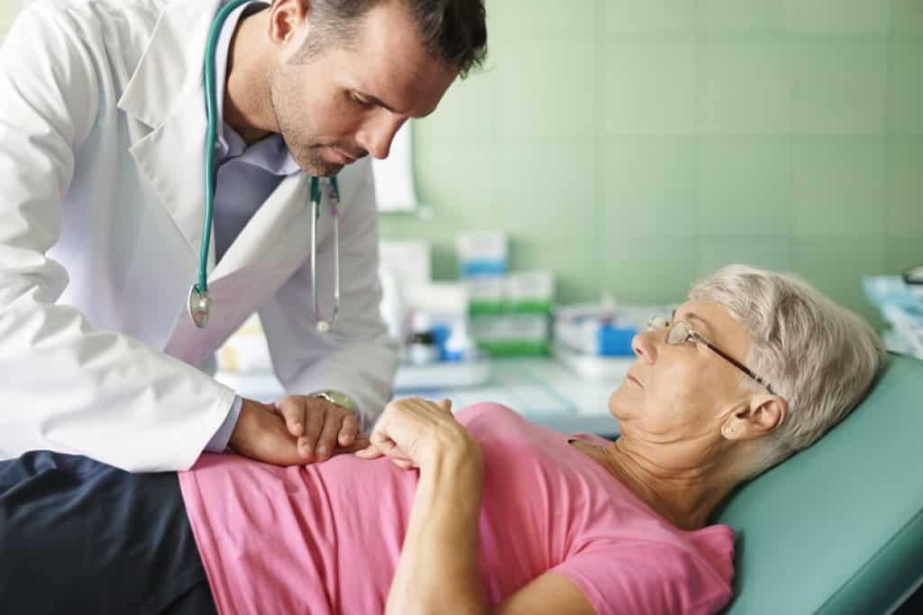 אישה מבוגרת עם חולצה ורודה ומשקפיים בבדיקה אצל הרופא