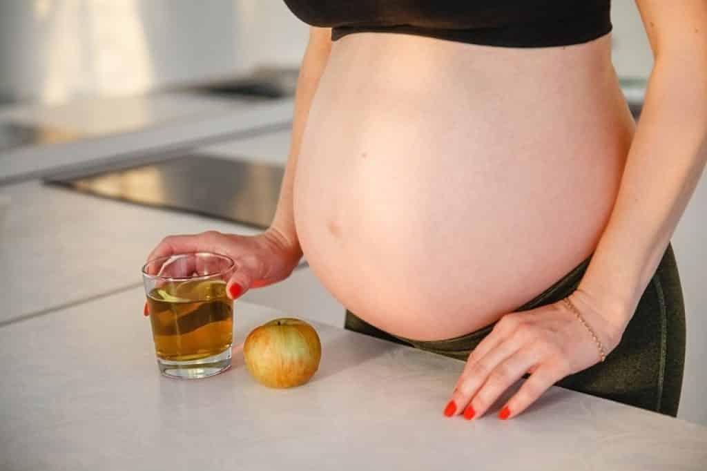 אישה עומדת במטבח ומחזקה כוס מיץ תפוחים