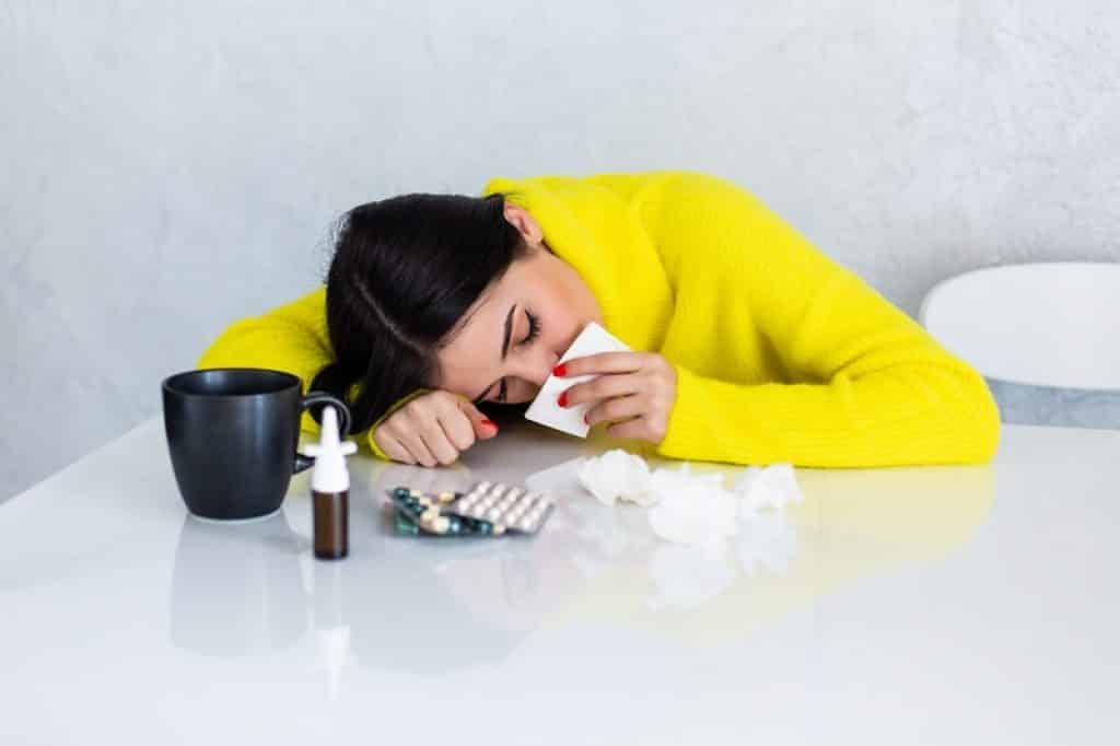 אישה עם חולצה צהובה ולידה תרופות וכוס תה