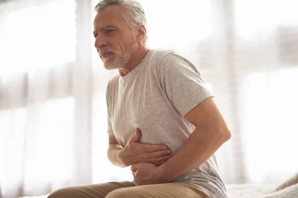 איש מבוגר סובל מתופעות של וירוס בבטן