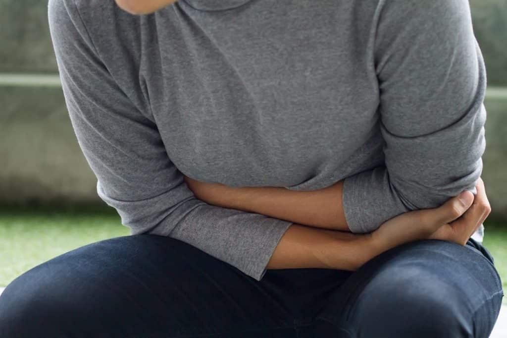 איש עם חולצה אפורה עם כאבי בטן של עצירות