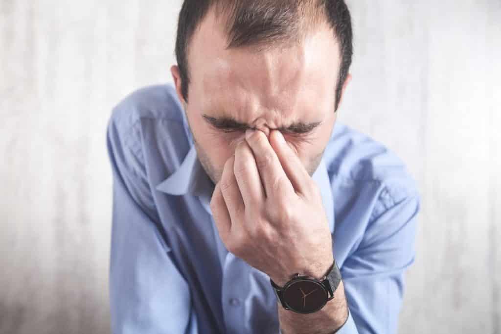 איש עם סינוסיטיס סובל מכאבים באף