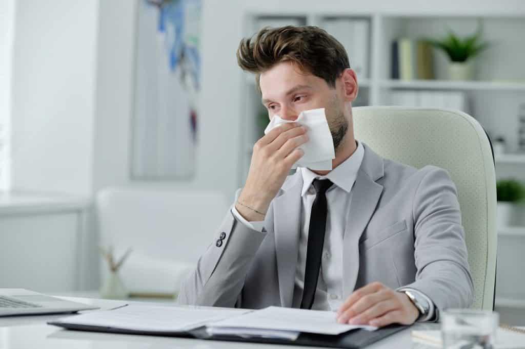איש עסקים יושב על כיסא משרדי לבן ומנגב נזלת