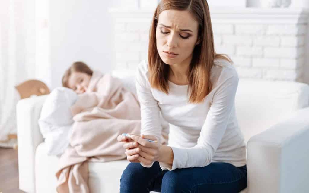 אמא יושבת מוטרדת בזמן שהבת שלה עם מחלת הפה והגפיים