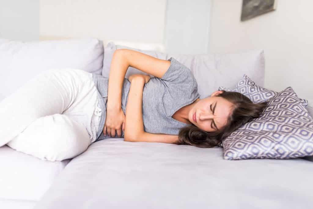 בחורה צעירה נחה במיטה עם מצעים אפורים