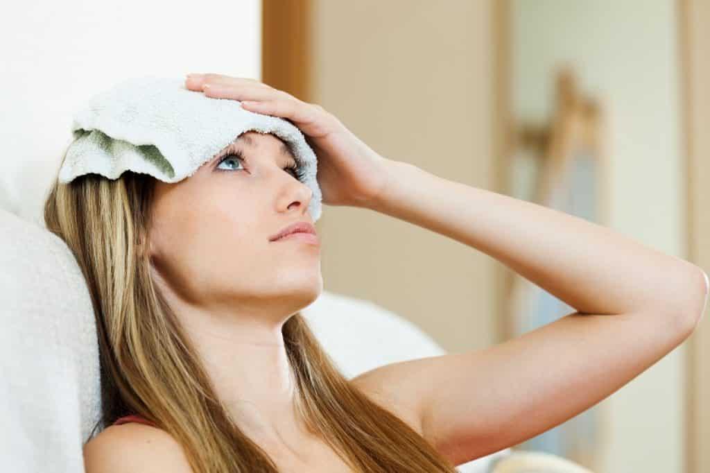 בחורה שוכבת במיטה עם מגבת רטובה במים חמים על המצח