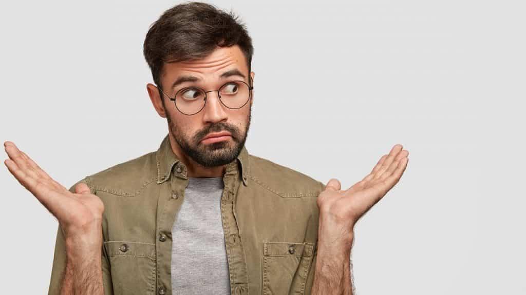 בחור עם זקן ומשקפיים בהבעת פנים של שאלה