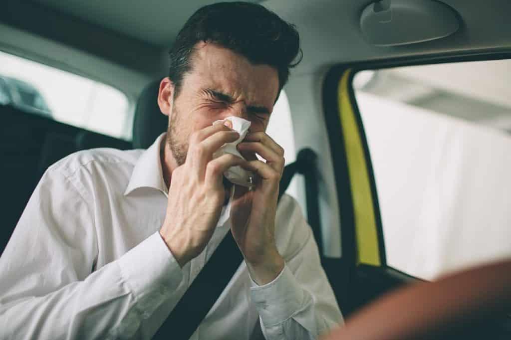 בחור עם סינוסיטיס מקנח את האף בזמן נהיגה
