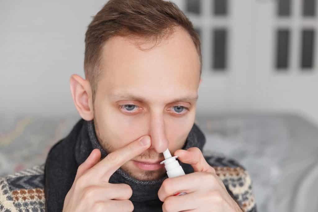 בחור צעיר מנסה להקל על האף עם תרסיס
