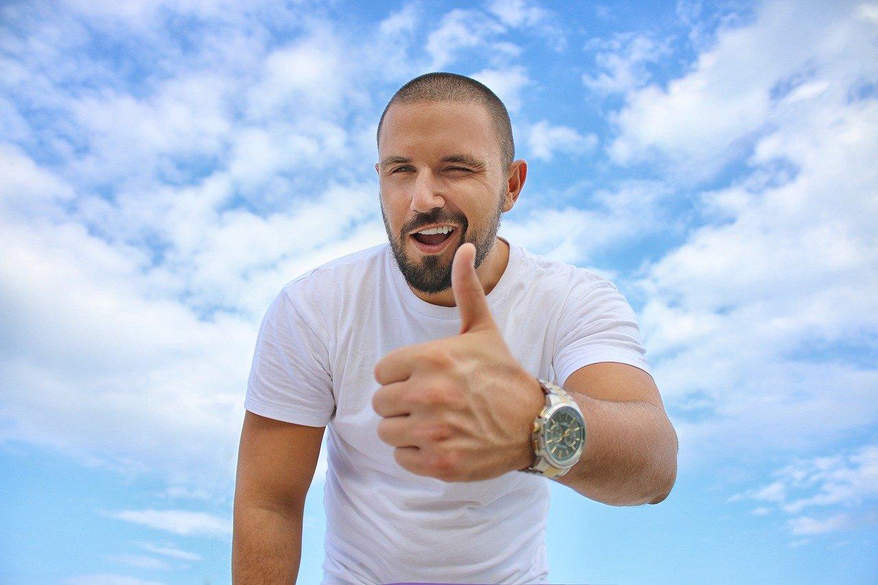גבר צעיר מחייך על רקע שמיים כחולים ומרים אצבע