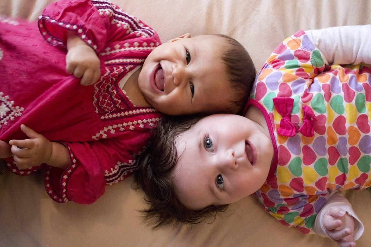 זוג תינוקות על מיטה מחייכים