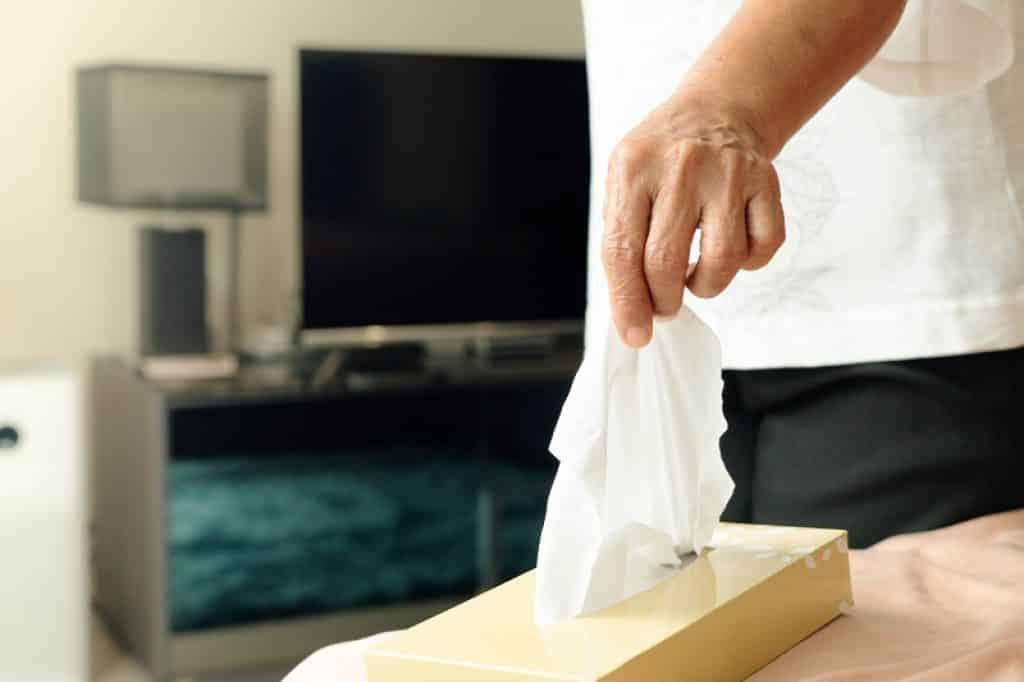 יד של גבר מוציאה טישו מתוך חבילה שמונחת על השולחן