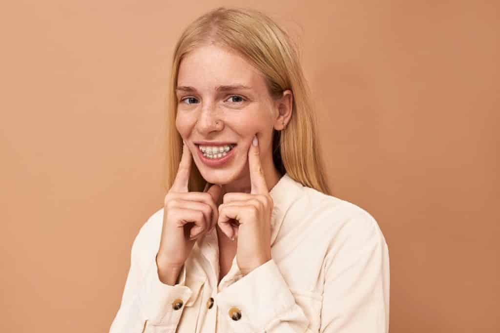 ילדה מחייכת עם שתי אצבעות על הלחיים על רקע ורוד