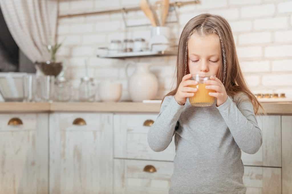 ילדה עם מחלת הפה והגפיים שומרת שותה מיץ תפוזים במטבח