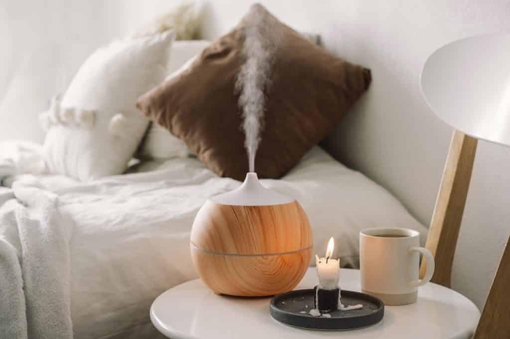 מכשיר אדים, נר וכוס תה מונחים על שולחן עגול