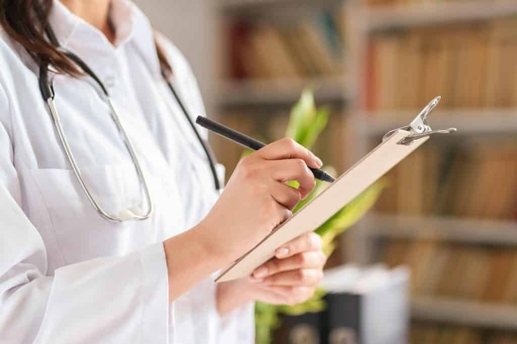 רופאה מחזיקה לוח קשיח עם רשימה של בדיקות