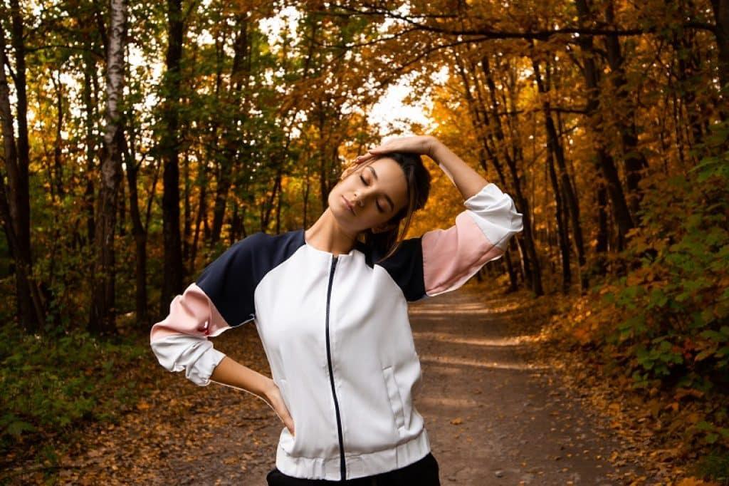 בחורה עם גקט ביער עושה מתיחות תוך כדי הליכה