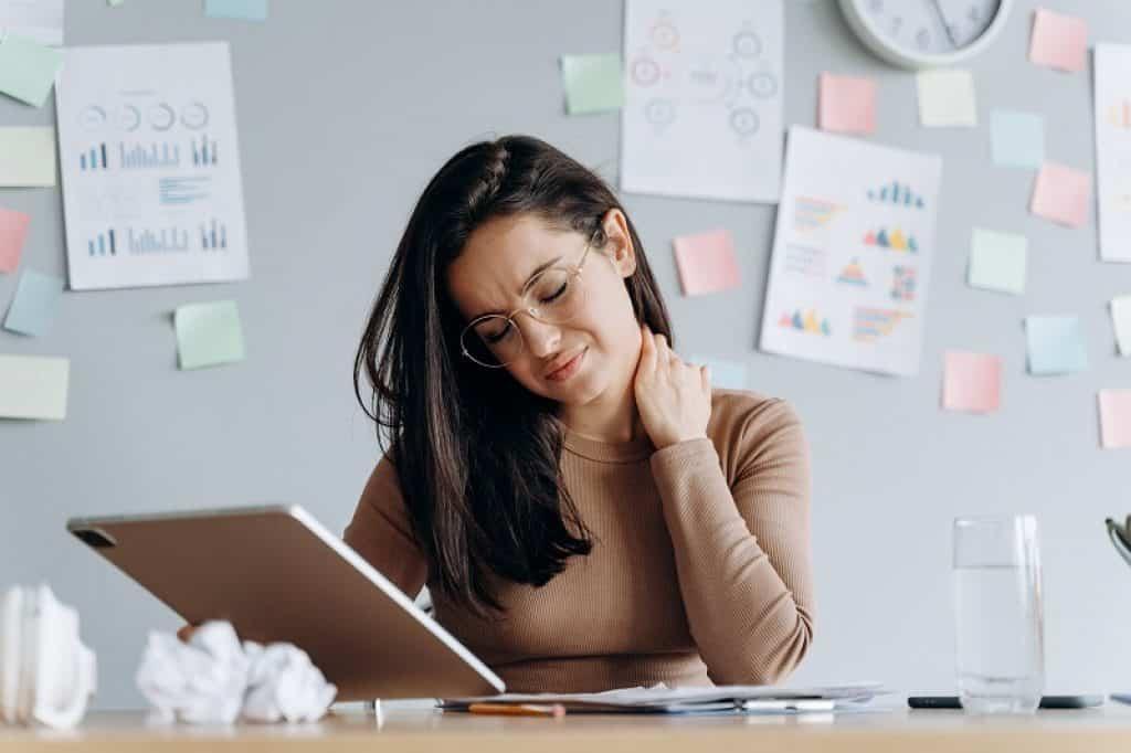 בחורה עם משקפיים בעבודה יושבת עם כאבי צוואר
