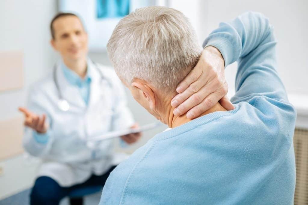 בחור מבוגר יושב אצל רופא ומחזיק את העורף